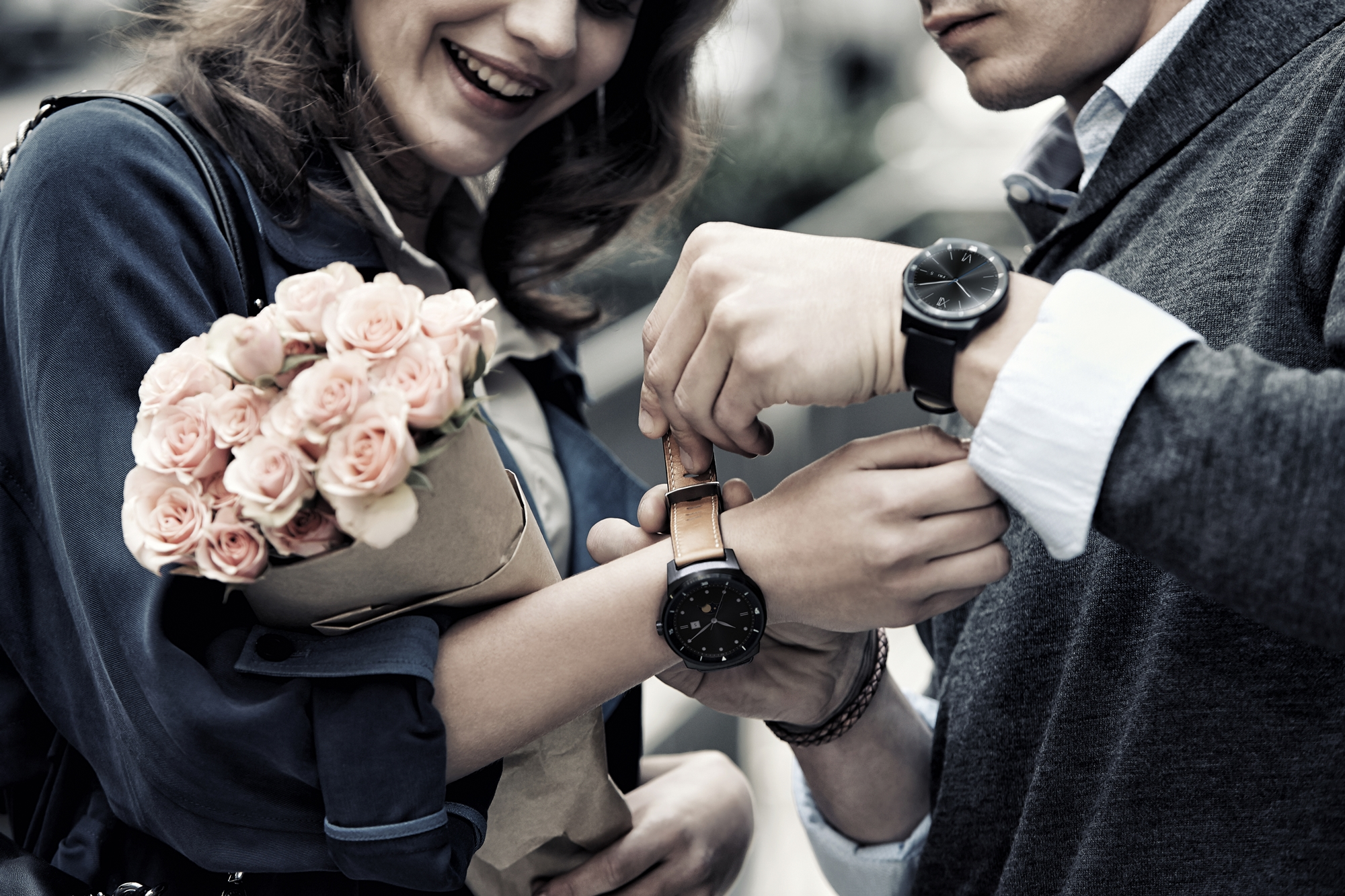A man wearing the LG G Watch R as he puts another LG G Watch R on his girlfriend's wrist.