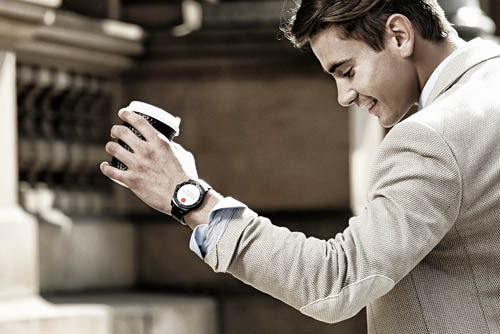 A man wearing a LG G Watch R is holding a cup of coffee.