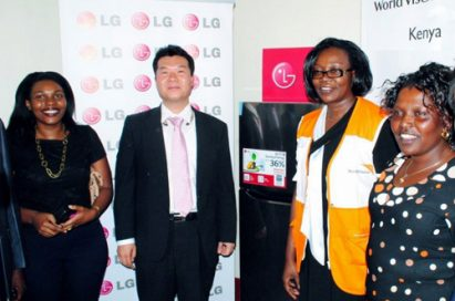 People from LG and World Vision Kenya standing in front of the LG solar powered refrigerator equipped with Smart Inverter Compressor