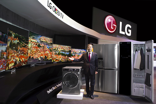 LG representative stands right in front of the diverse range of products across LG's consumer electronics and home appliances.