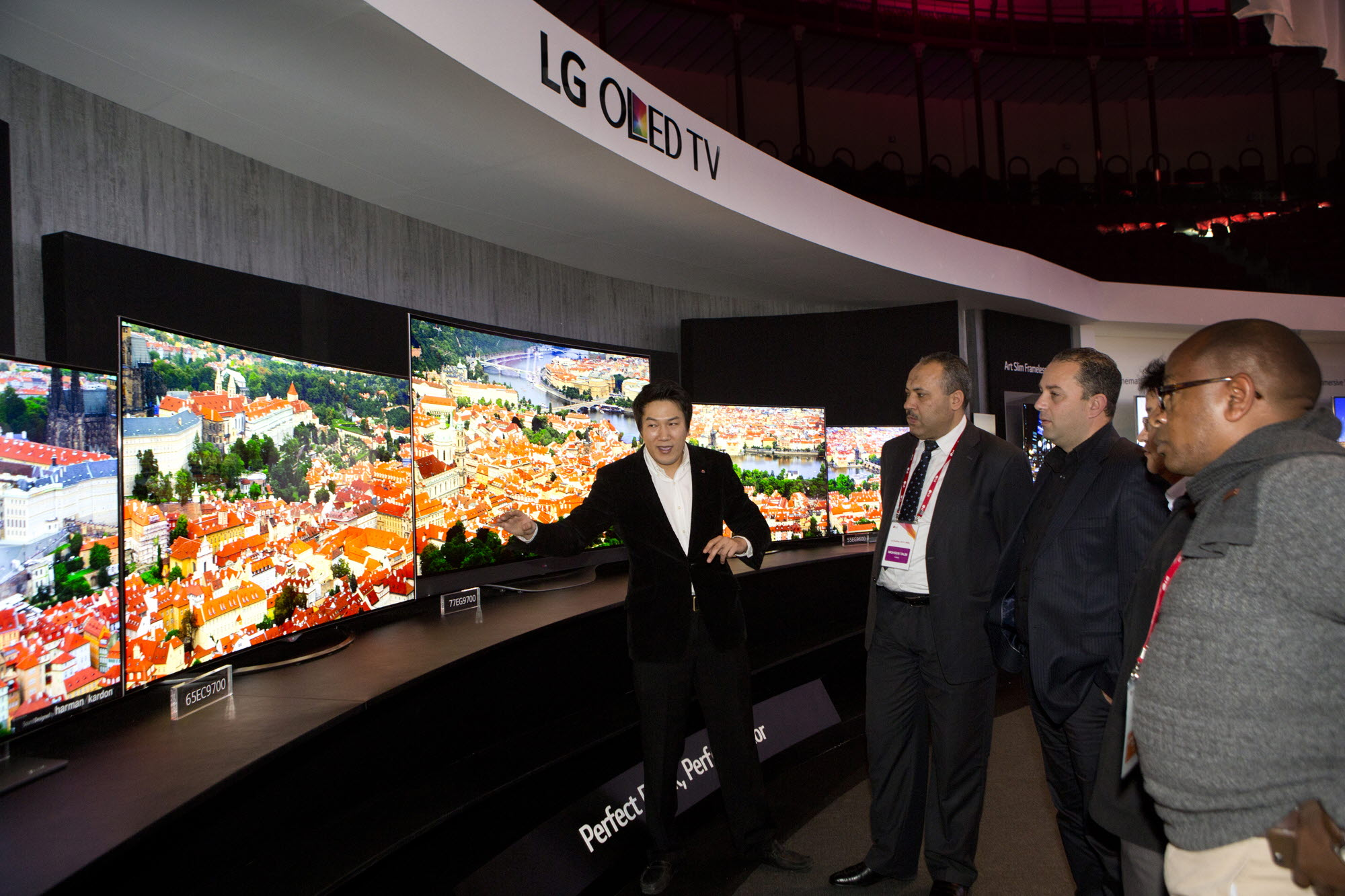 A guide explains the LG's flashship 4K OLED TV lineup to visitors.
