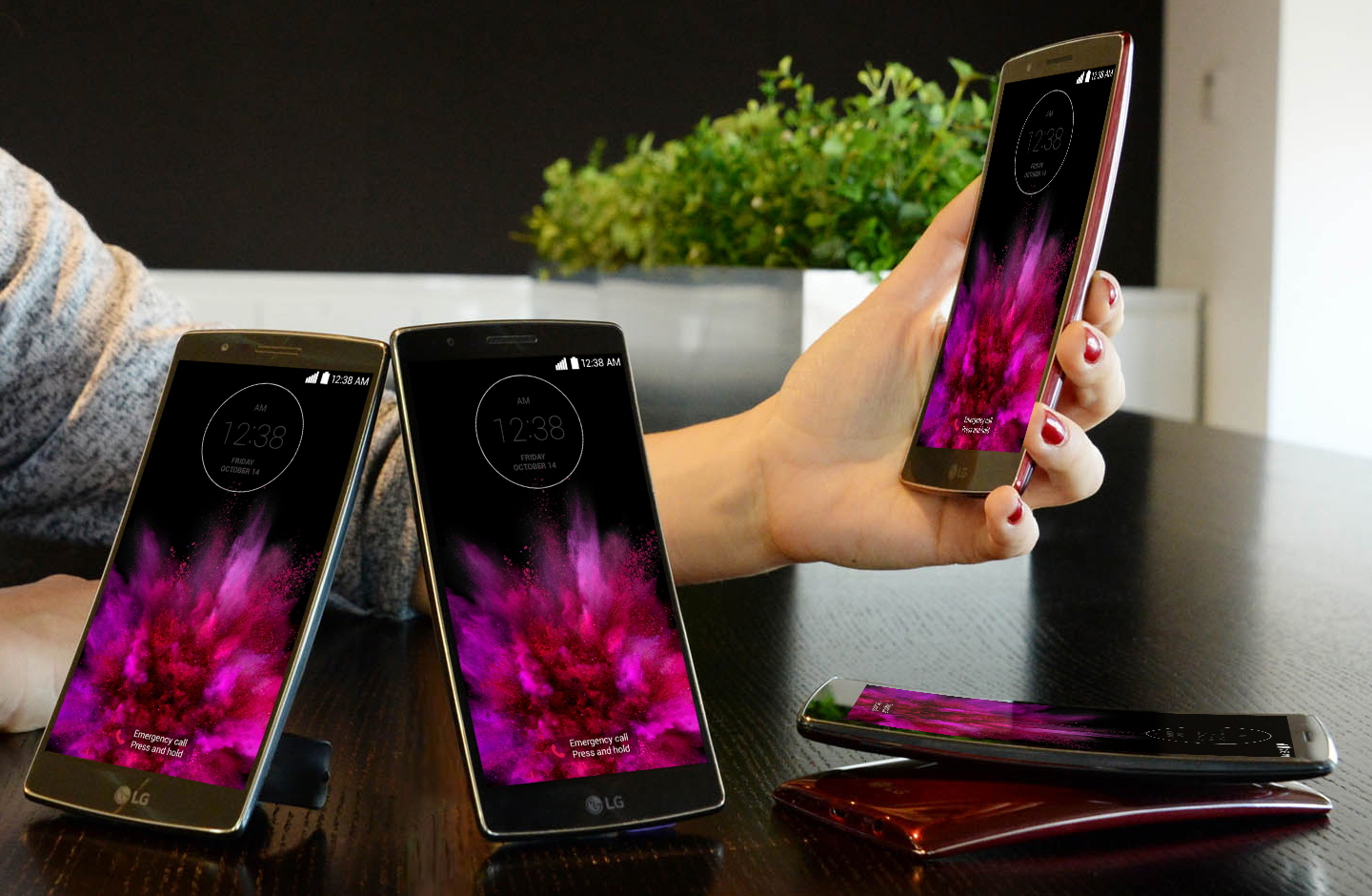 A model is putting her arm down on a table holing a LG G Flex2. And two LG G Flex2s are standing on the table showing their fronts and other twos are lying on the table – each showing front and back.