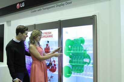Two models opening LG's Transparent Display Cooler Door at ISE 2015