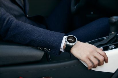A side view of a man sitting in the driver's seat while wearing the LG Watch Urbane LTE.