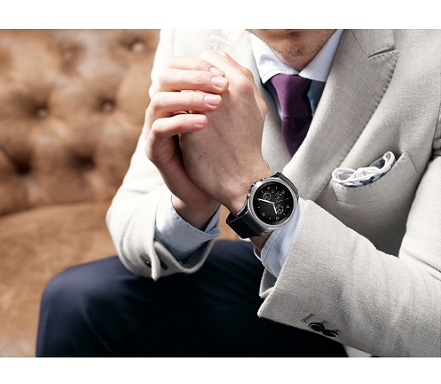 A man in suit holds his hands wearing LG Watch Urban LTE on the left hand.
