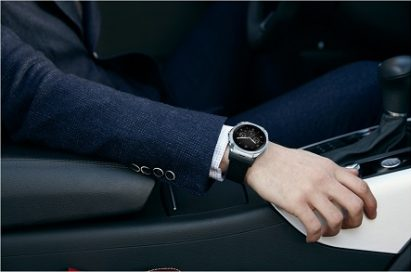 A man in suit rests his right hand on the arm rest inside a vehicle wearing LG Watch Urban LTE.