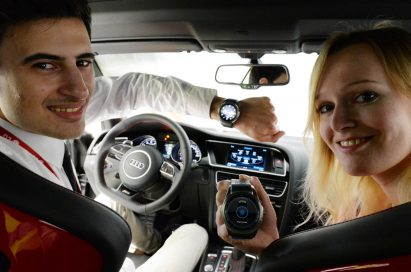 Two models sit in a car, the man wearing the LG Watch Urbane and woman holding one while posing for the camera