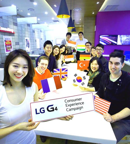 "A group of people from all around the world sit around a table behind a model holding up a ""LG G4 Consumer Experience Campaign"" sign."