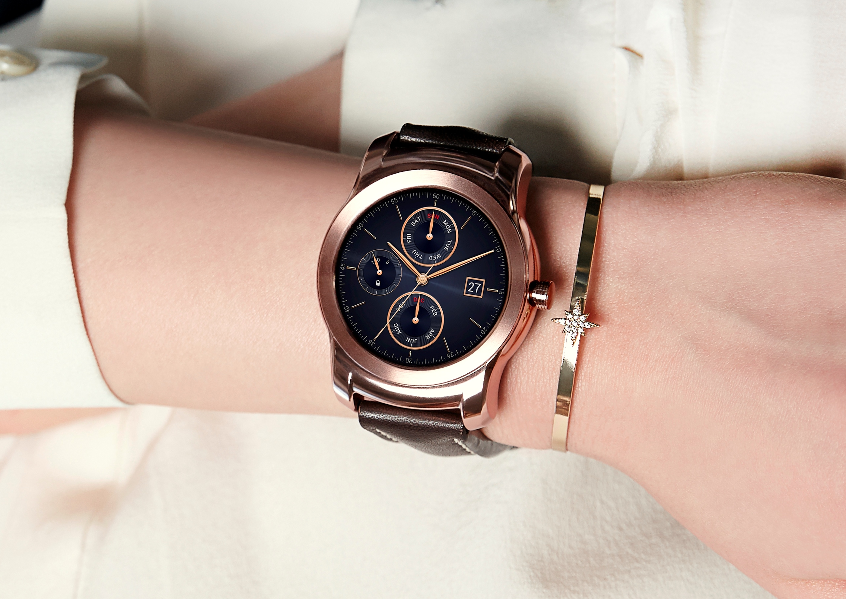 A close-up of a woman's wrist while wearing the Rose Gold LG Watch Urbane and a matching gold bracelet.