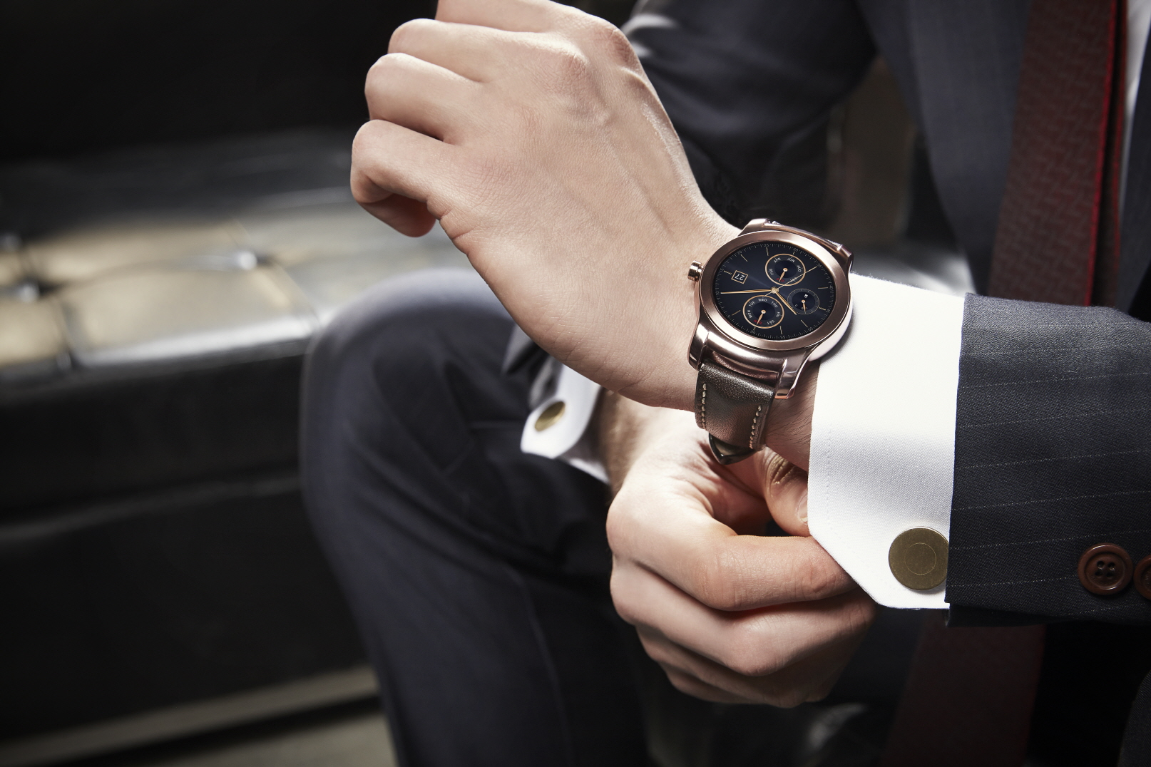 A man in suit tidies up the sleeve while wearing LG's Watch Urban.
