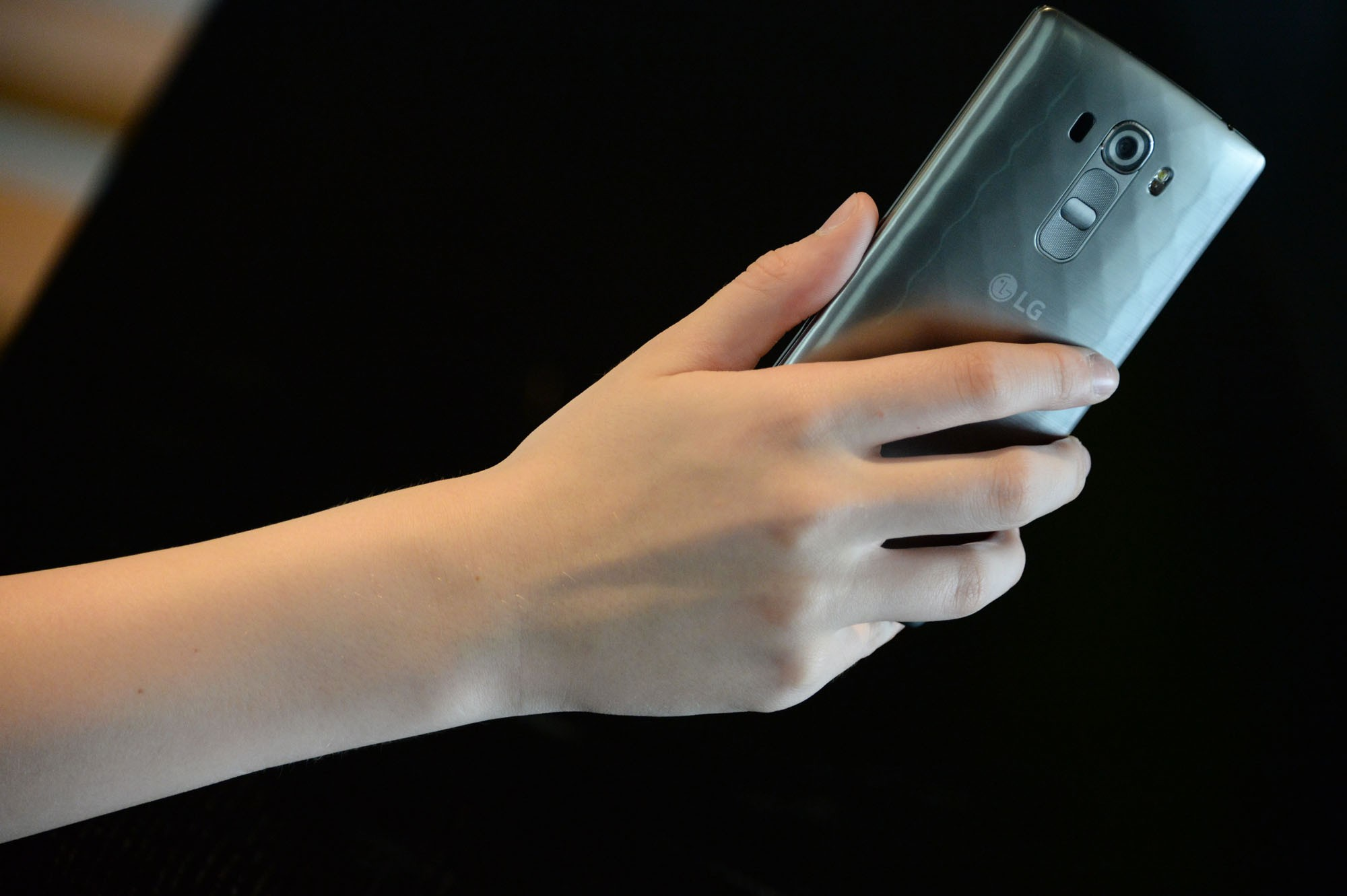 A close-up of a woman holding the LG G4 Beat in Metallic Silver color, showing its rear side.