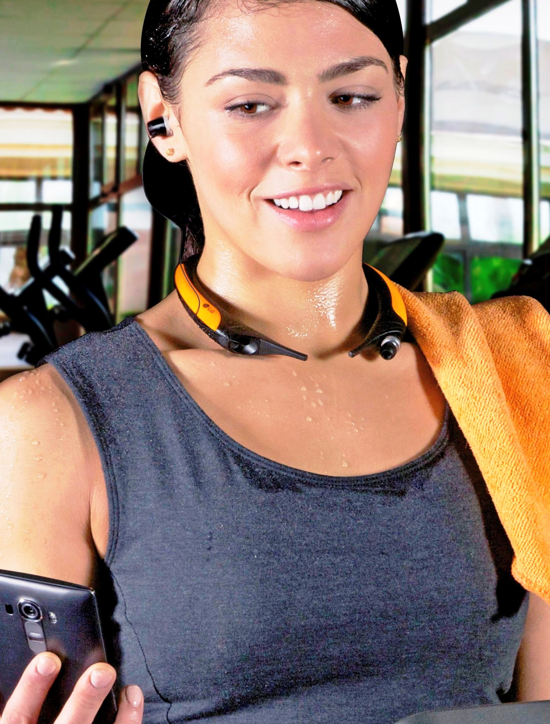 A woman looks at her smartphone while wearing the LG TONE Active as she takes a break from an intense gym session.