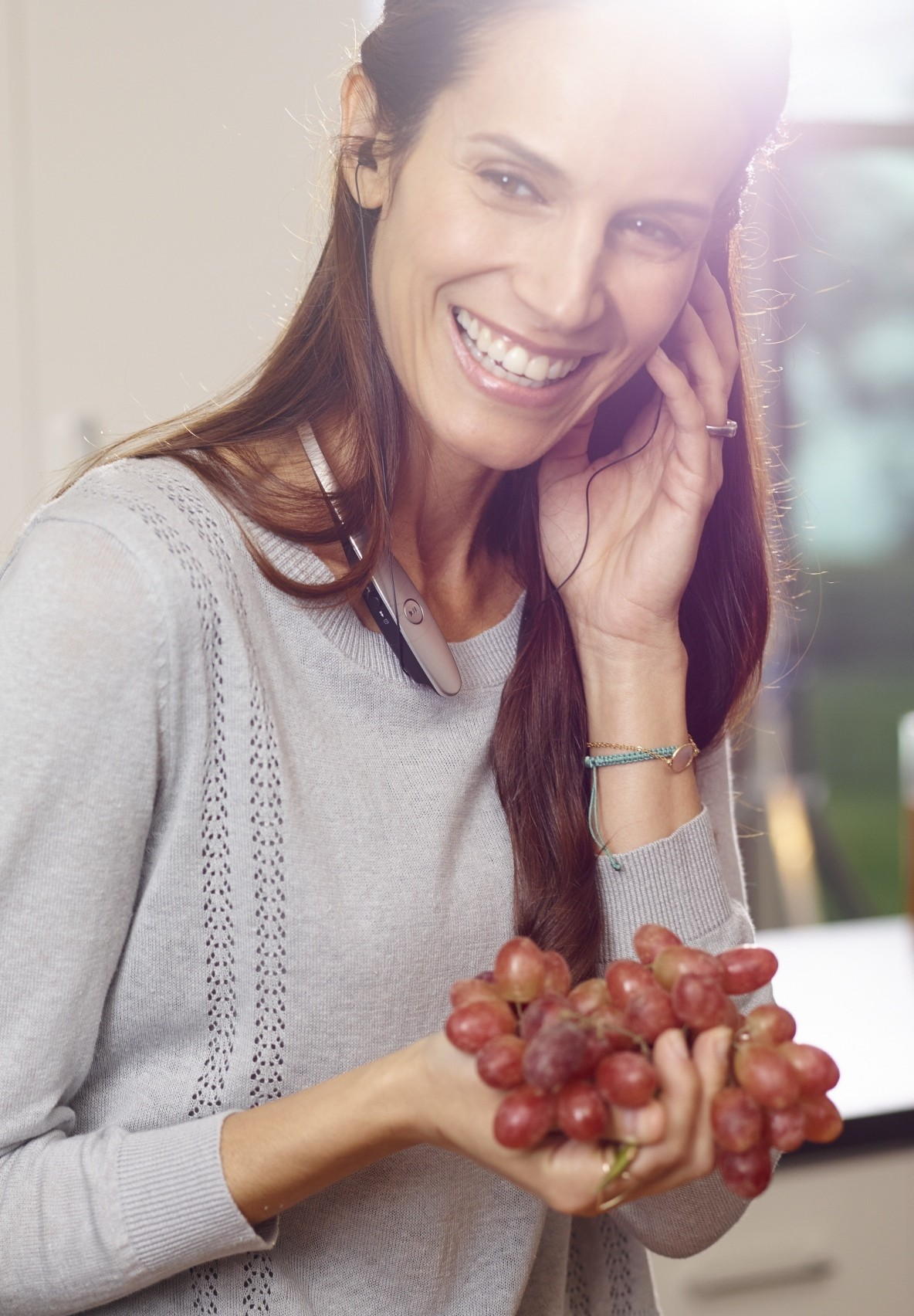 A woman talking on her phone through a LG TONETM Bluetooth headset while holding grapes in her hand.