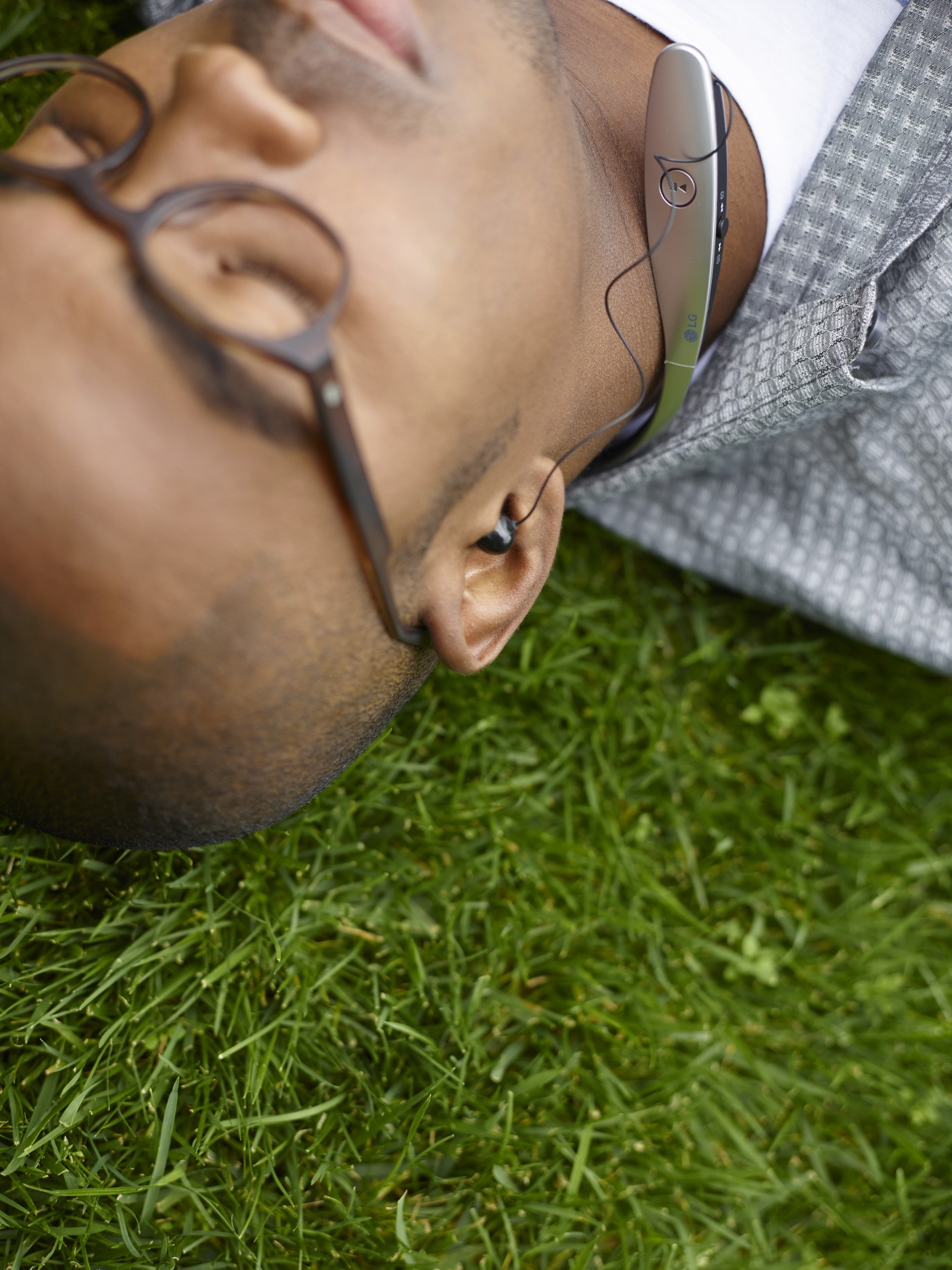 A man enjoying music with the LG TONETM Bluetooth headset while lying in the grass.