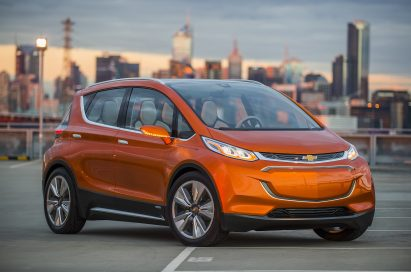 The Chevrolet Bolt EV (electric vehicle) with a city skyline backdrop.