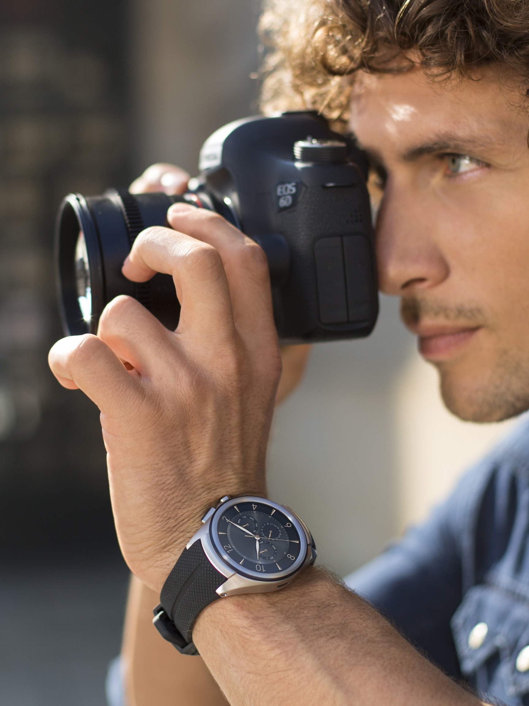 A man with the LG Watch Urbane 2nd Edition on his wrist takes a photo with a DSLR camera