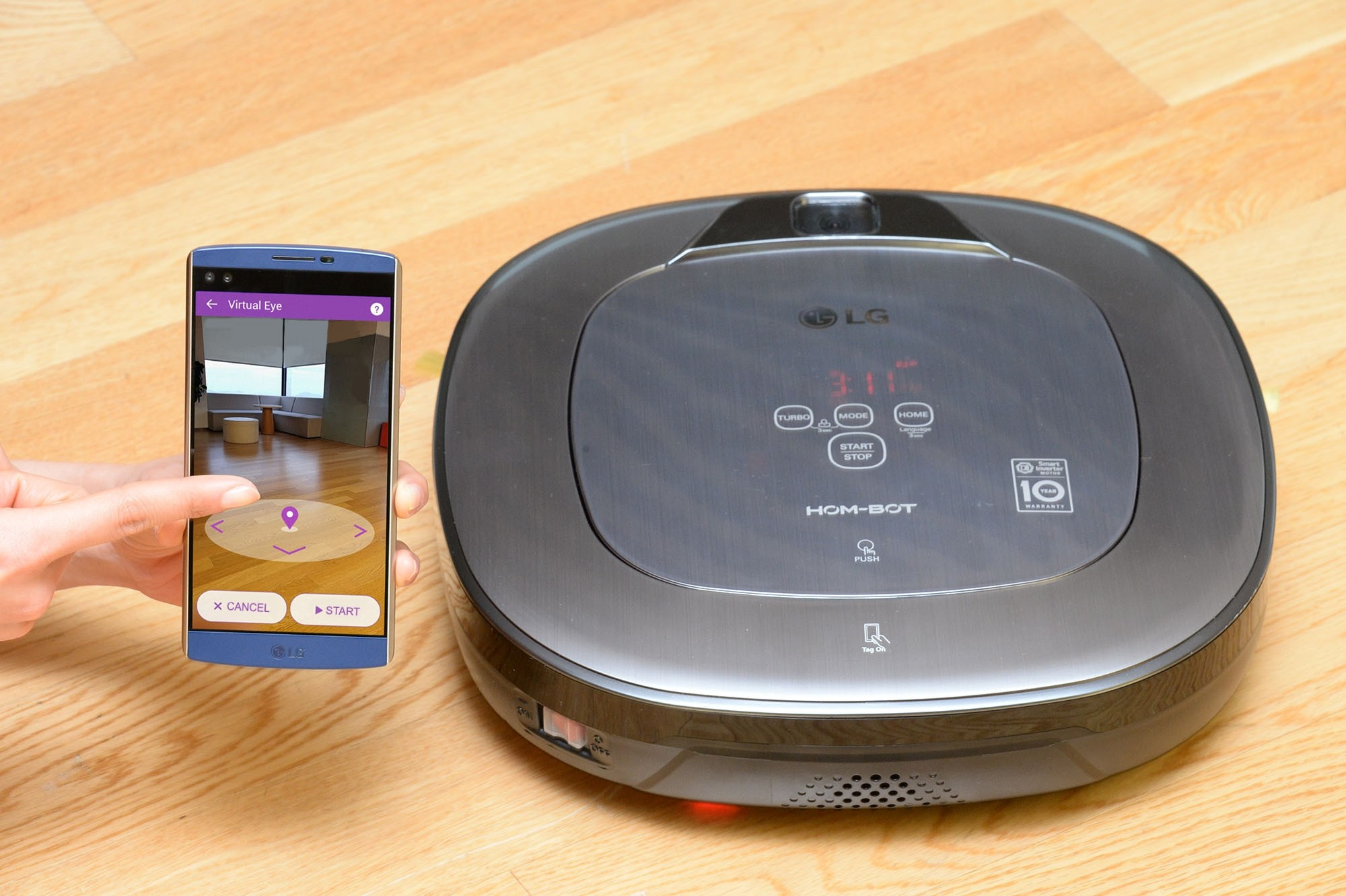 LG HOM-BOT and smartphone with hand visible showing its location