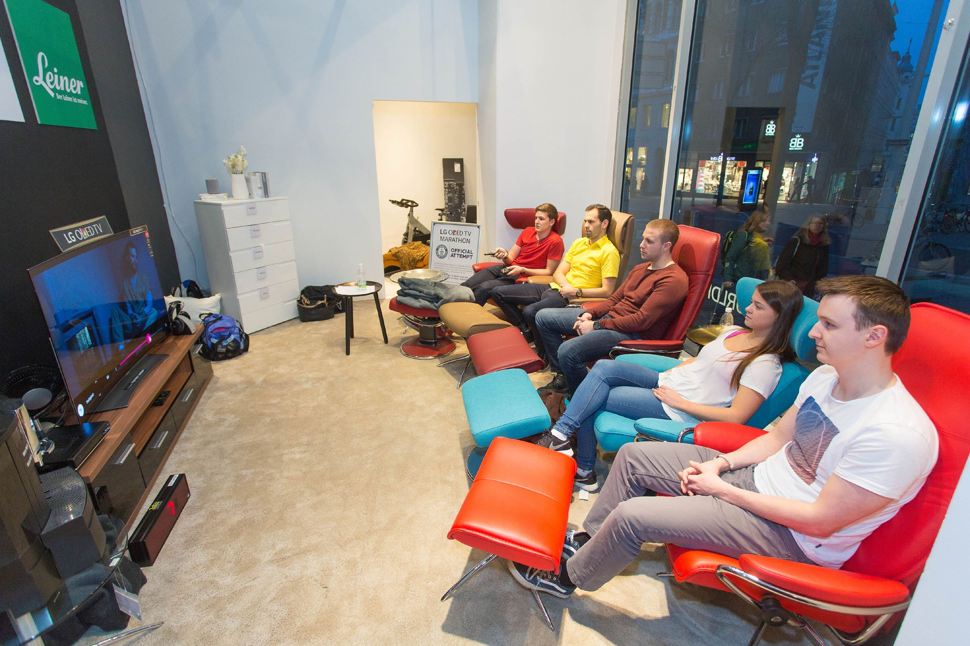 Five participants watch TV on one of LG's OLED TVs during their TV-watching marathon