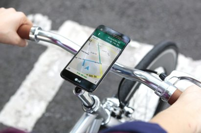 A biker is receiving directions from the LG X screen, which is fixed on the top of the bike handle