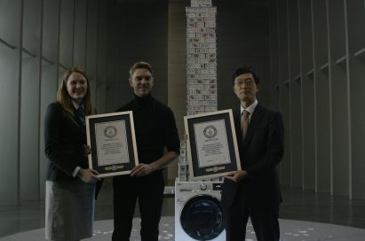 Three people holding Guinness World Record certification in front of LG Centum System™ washing machine with house of card built on it