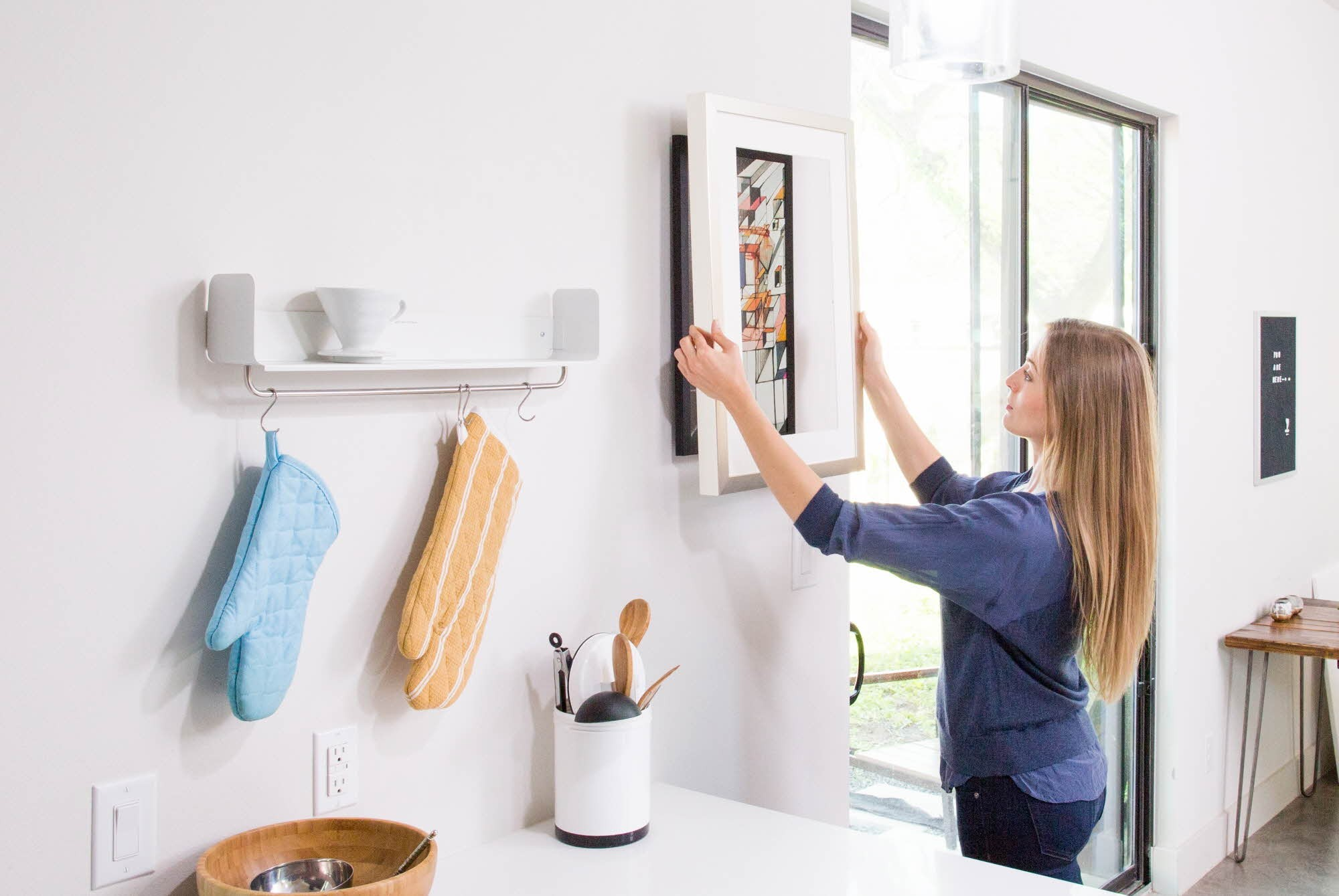 A woman effortlessly hangs up her new cord-free digital frame by Acanvas.
