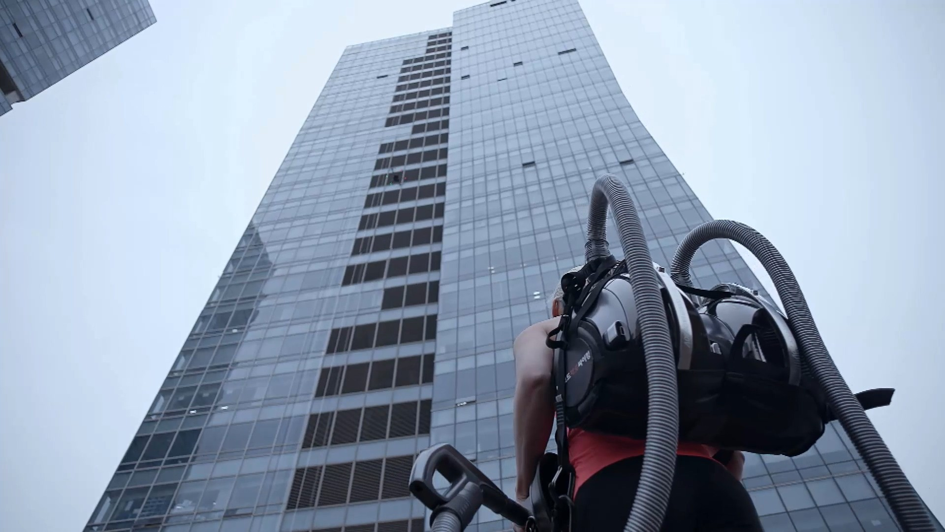 Professional rock climber Sierra Blair-Coyle with LG CordZero™ canister vacuum standing in front of 33-story office tower