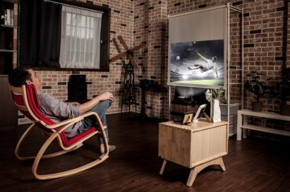 A man leans back in his chair while watching sport with the LG Minibeam projector