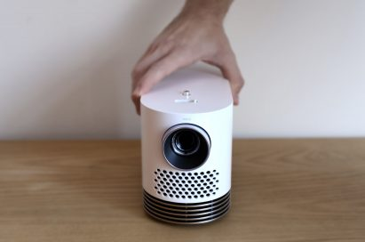A hand grabbing the LG ProBeam from the top