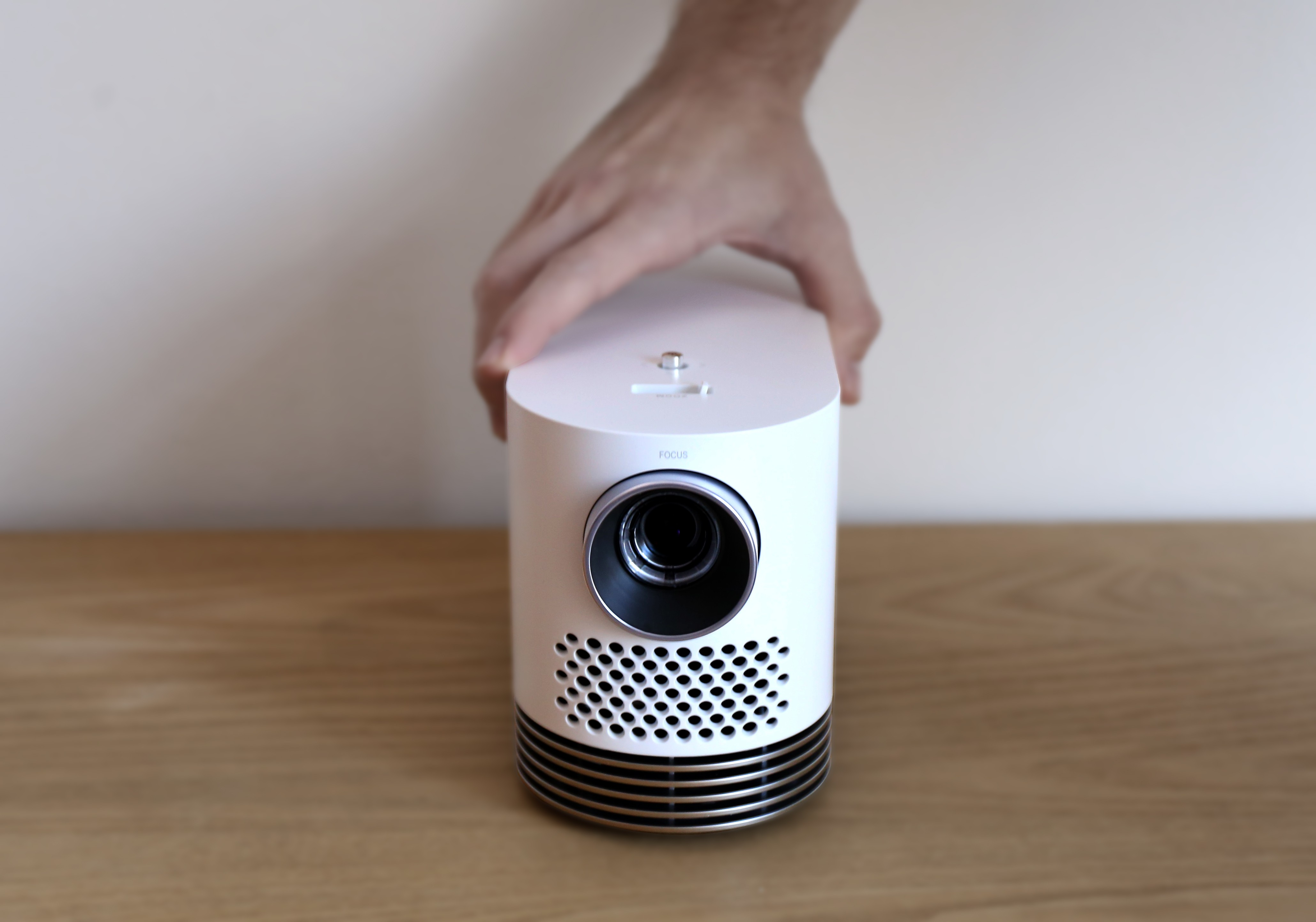 Front view of LG Probeam Laser Projector (model HF80J) being put on the desk by a man's hand