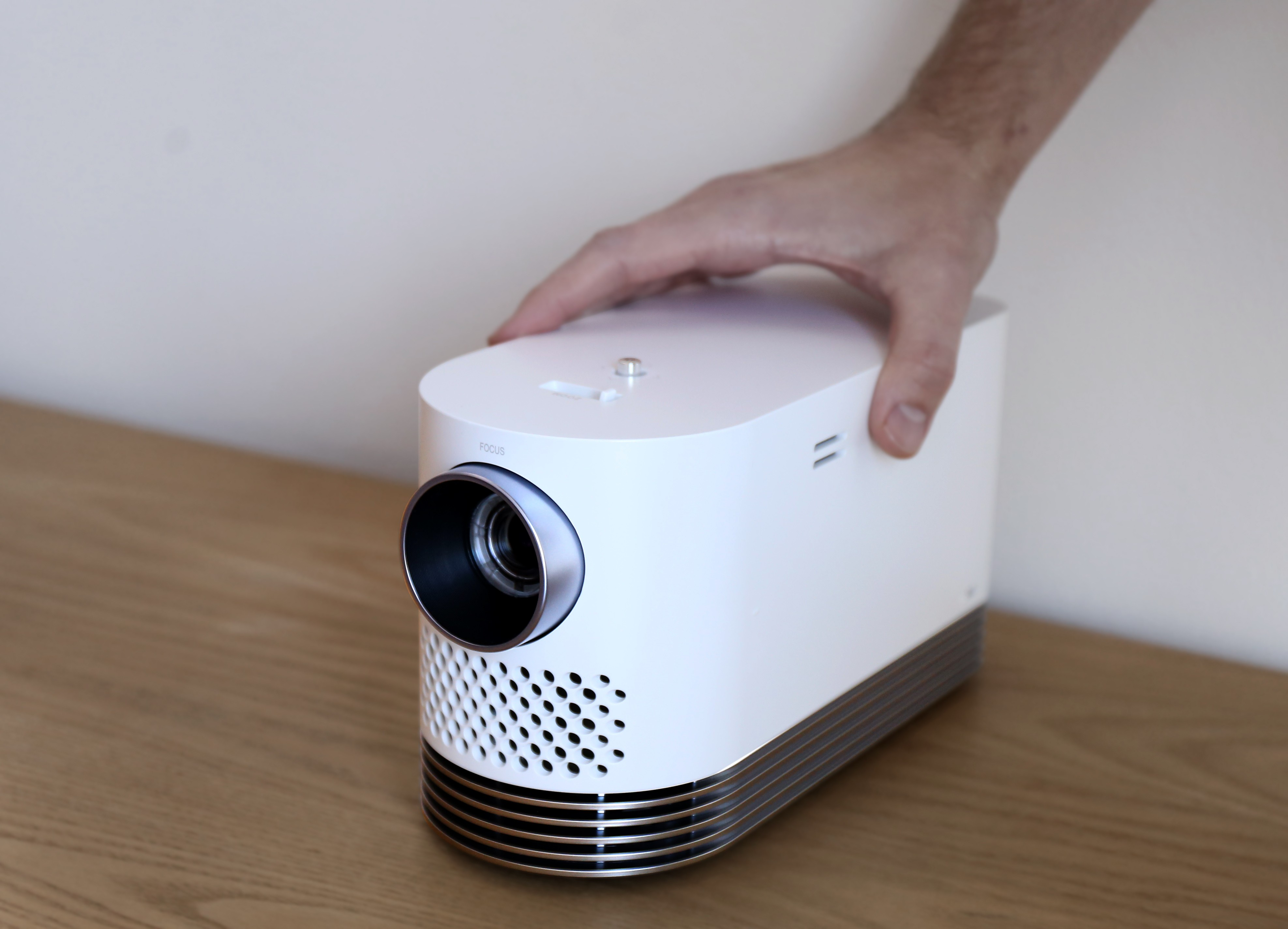 Front view of LG Probeam Laser Projector (model HF80J) facing 15 degrees to the left while being touched by a man's hand