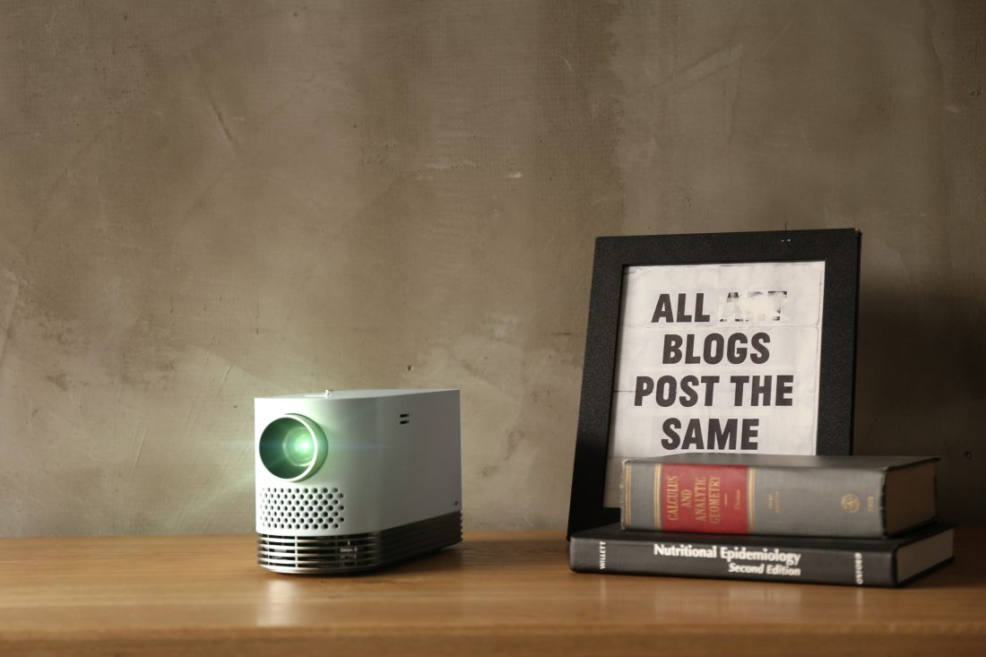 Front view of the LG Probeam Laser Projector (model HF80J) on a table next to books