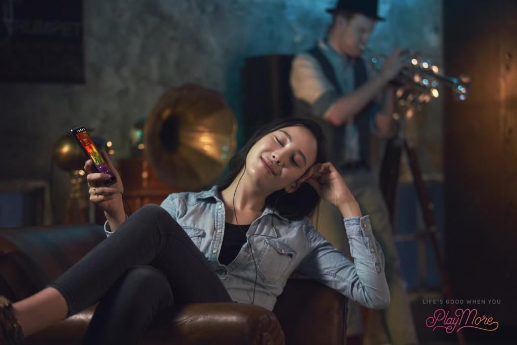 A woman relaxing in a chair and listening to music with Spatial Audio via smartphone with headphones on