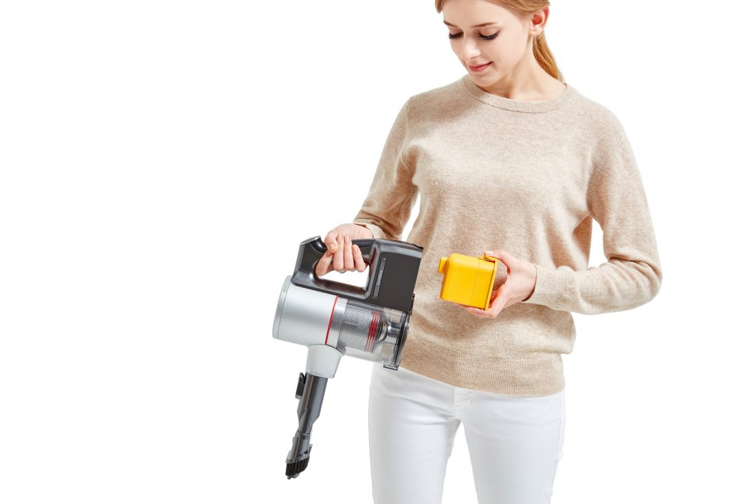 A woman is detaching the battery from the bottom of canister on the LG CordZero Handstick.