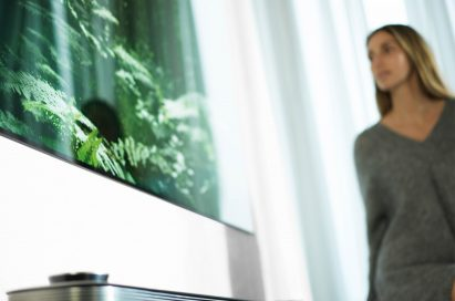 A woman stands looking at the LG SIGNATURE OLED TV W (model W7)