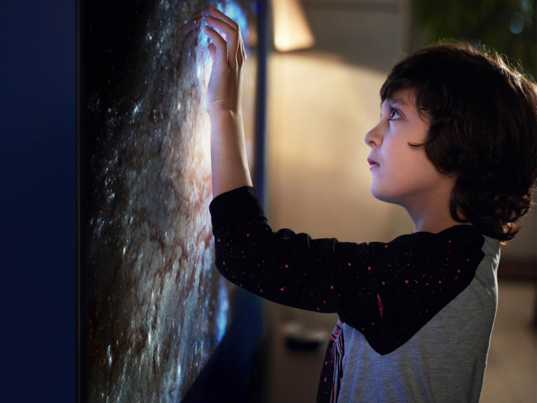 A small boy touches the screen of the LG SIGNATURE OLED TV W, there is a picture of a galaxy on the screen.