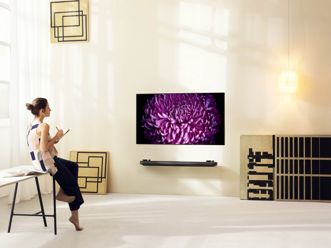 A woman rests against the table looking at an LG SIGNATURE OLED TV W (model W7) mounted on the wall.