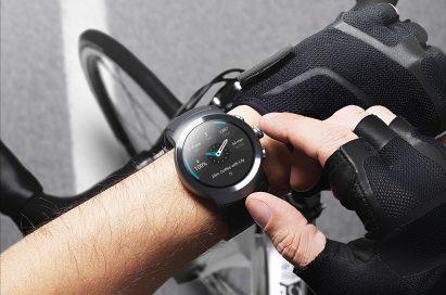 A man touching his LG Watch Sport in Titanium while taking a break from cycling