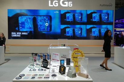 Two LG G6 devices and 31 booth awards given to the LG G6 at MWC 2017 in front of a screen showing off LG G6's dual wide-angle cameras
