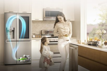 A mother and daughter stand in their kitchen with the LG InstaView™ refrigerator with Inverter Linear Compressor behind them