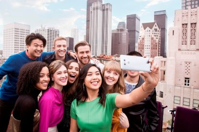 A group of people take a group selfie with the LG G6 in Ice Platinum in front of the New York skyline