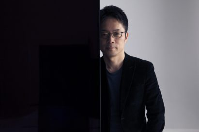 Tokujin Yoshioka stands behind one of LG screens making up his art installation wall looking into the camera.
