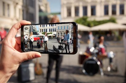 A person taking a picture with the LG Q6 of a band performing