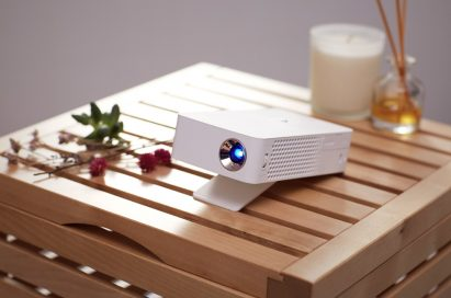The LG MiniBeam Projector model PH30J on a wooden stool