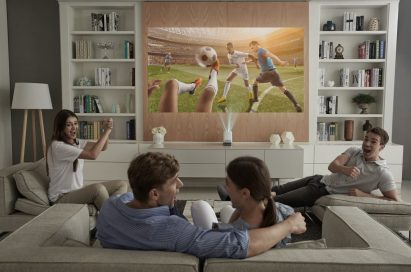A group of friends use the LG Probeam Projector to watch sport in the living room