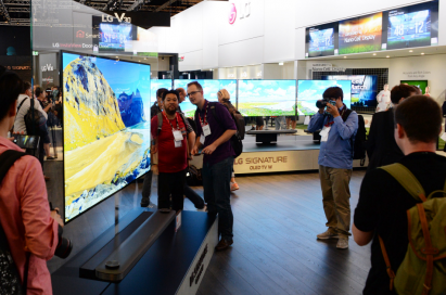 Visitors to LG IFA booth examining the minimal depth of LG SIGNATURE OLED TV W