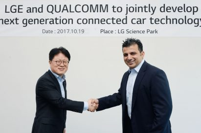 Kim Jin-yong, executive vice president of LG's Vehicle Components Smart Business Unit, shake hands with Nakul Duggal, vice president of product management at Qualcomm Technologies, Inc, to celebrate the new agreement