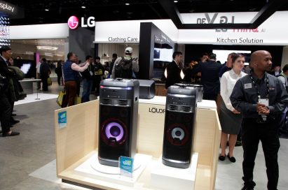 Staff stand next to a display of two LG LOUDR speakers, with several CES attendees looking at LG ThinQ AI kitchen solutions in the background