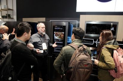 A gentleman explains the main features of the LG InstaView Door-in-Door Refrigerator to three visitors