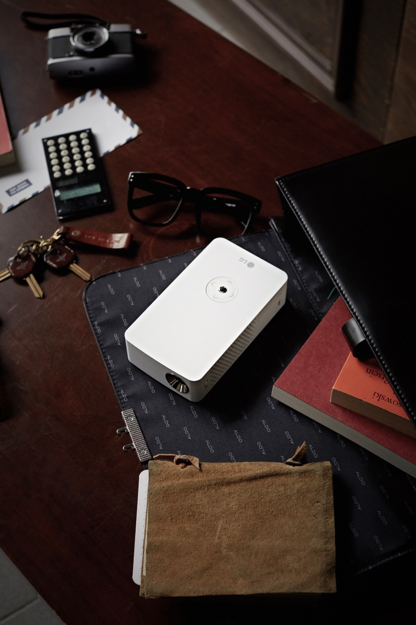 Top view of the LG MiniBeam Projector PH30J on a desk with some items for scale