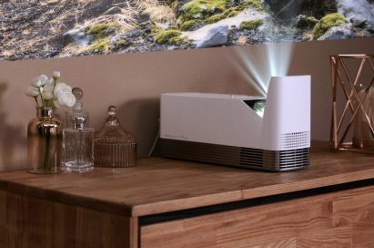 An LG ProBeam Projector HF85J is put next to some perfumes on a cabinet, projecting an image on the wall.